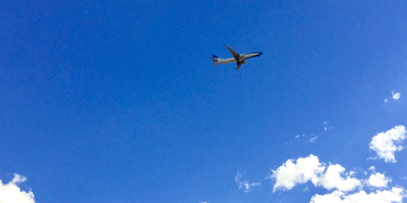 Airplane up in a blue sky above white clouds. Photo: Hans Uhrus