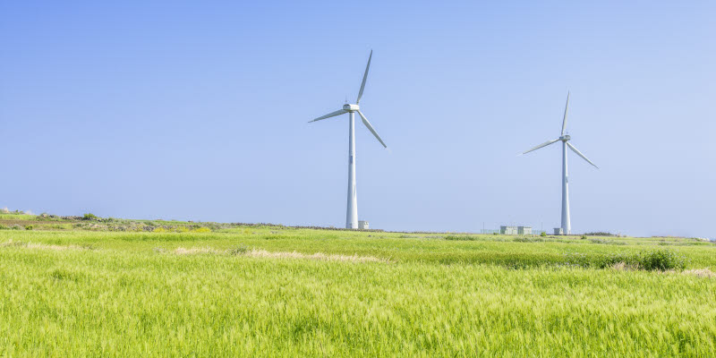 windmill on a green meadow with blue sky