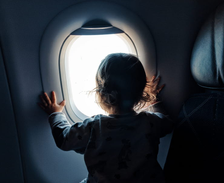 Child looking out through aircraft window