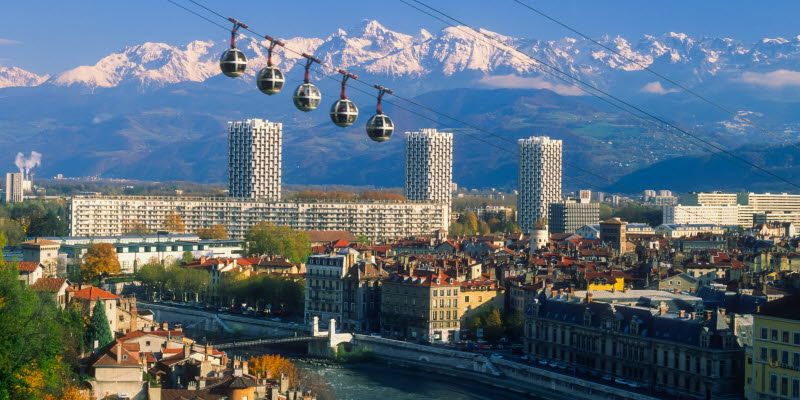City of Grenoble with a river, houses and alps in the background