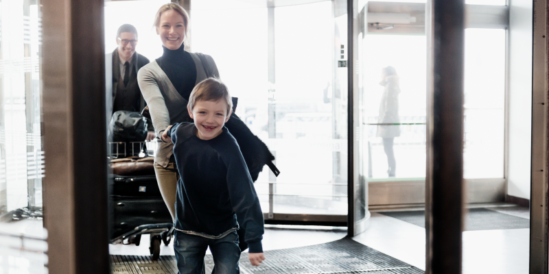 Boy holding woman's hand at the entry of a terminal at Stockholm Arlanda