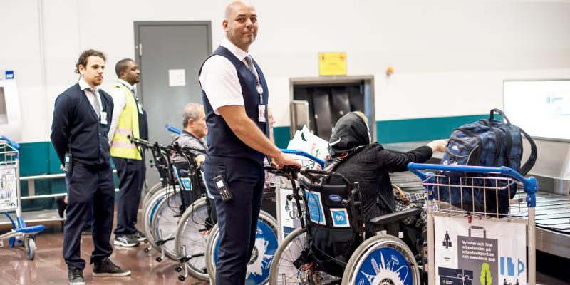 Ledsagare och tre rullstolar vid ett bagageband