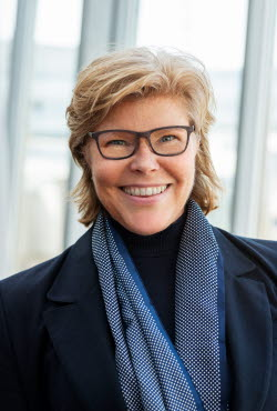 A photo of Katrin Bäckman, a blond woman with glasses and a blue scarf