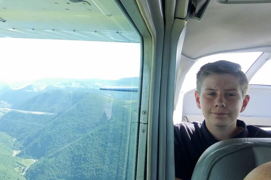 Pojke tittar ut från flygplan på grönklädda berg