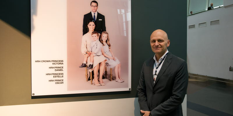 Peder Grunditz poses in front of the new portrait of the Crown Princess family