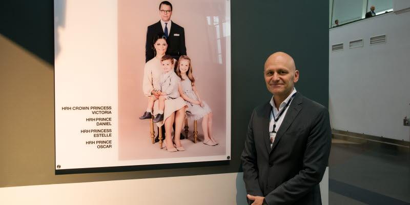 Peder Grunditz poserar framför det nya porträttet på kronprinsessfamiljen