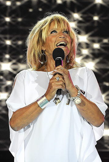 Barbro Lill-Babs Svensson in a white blouse holding a microphone
