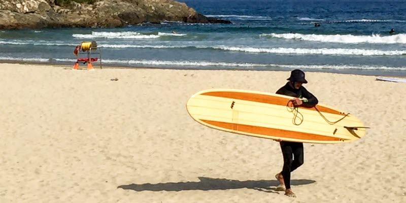 Människa med surfingbräda på en strand